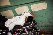 A Vietnamese man sleeps on his motorbike in the Old Quarter of Hanoi, Vietnam, Southeast Asia.