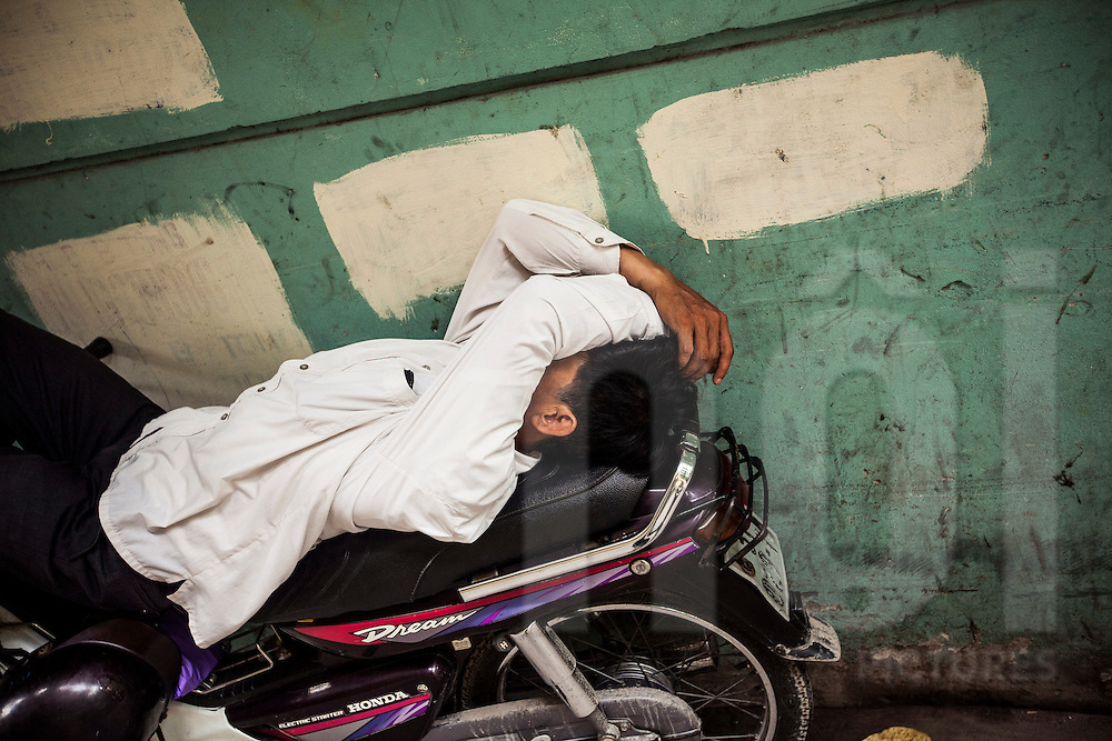 A Vietnamese man sleeps on his motorbike in the Old Quarter of Hanoi, Vietnam, Southeast Asia.