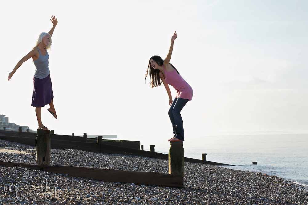 Two young women balancing on wooden wave breakers on beach