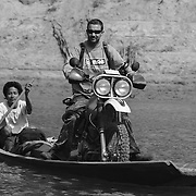 Motorbike tour leader Digby Greenhalgh crosses the Bangphai River the old fashioned way. The Bangphai River was a very important river crossing for Vietnamese troops ferrying supplies south along the Ho CHi Minh Trail.