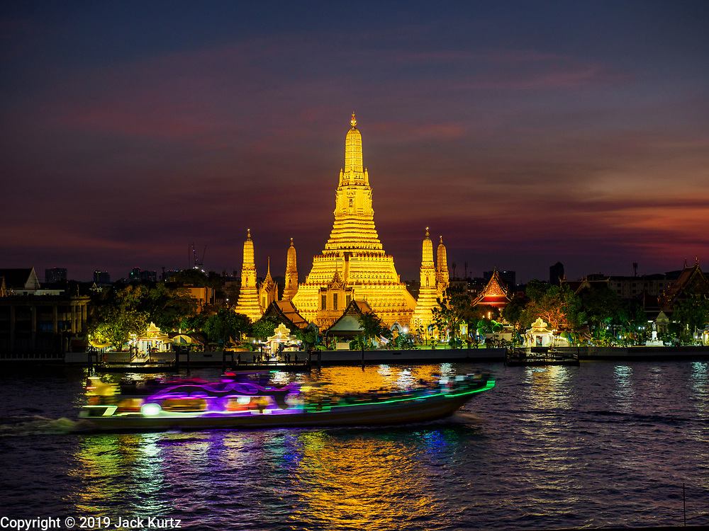 "06 MARCH 2019 - BANGKOK, THAILAND:  Boat traffic on the Chao Phraya River goes past Wat Arun just after sunset. Wat Arun Ratchawararam Ratchawaramahawihan or Wat Arun (""Temple of Dawn"") is a Buddhist temple (wat) in Bangkok on the Thonburi side of the Chao Phraya River. The temple derives its name from the Hindu god Aruna, who is personified as the rising sun. Wat Arun is among the best known of Thailand's temples. The temple has existed since at least the seventeenth century, but its distinctive prang (spires) were built in the Khmer style in the early nineteenth century during the reign of King Rama II.  PHOTO BY JACK KURTZ"