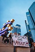 Frankfurt | 25 February 2017<br /> <br /> Am Samstag (25.02.2017) nahmen etwa 1000 Menschen in Frankfurt am Main an einer linksradikalen Demonstration unter dem Motto &quot;Make Racists Afraid Again&quot; Teil. Die Demo begann am S&uuml;dbahnhof in Frankfurt-Sachsenhausen und endete am Willy-Brandt-Platz. Organisiert wurde der Aufmarsch von dem B&uuml;ndnis &quot;Antifa United Frankfurt&quot;.<br /> Hier: Die Demo ist auf dem Willy-Brandt-Platz angekommen, Aktivisten mit einem Transparent mit der Aufschrift &quot;Faschos sind Haram / Kanax Antifa&quot; haben sich vor der Euro-Skulptur auf eine Mauer gesetzt.<br /> <br /> photo &copy; peter-juelich.com