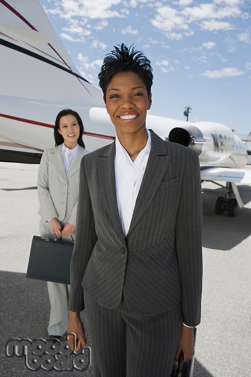 Portrait of two mid-adult businesswomen in front of private plane.