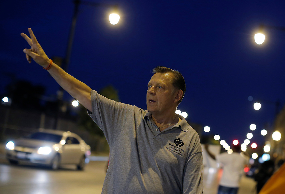 Father Michael Pfleger demonstrates in the streets during a weekly night-time peace demonstration in a South Side neighborhood in Chicago, Illinois, September 16, 2016.  REUTERS/Jim Young