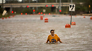 A woman who identified herself as Valerie walks along flooded President Street after leaving her homeless camp after Hurricane Matthew caused flooding, Saturday, Oct. 8, 2016, in Savannah, Ga. (AP Photo/Stephen B. Morton)