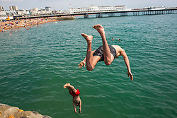 © Licensed to London News Pictures. 01/07/2016. Brighton, UK. Two young men jump in to the sea from a wall opposite Brighton pier. Thousand of visitors take to the beach in Brighton and Hove as hot and sunny weather hits the seaside resort. Photo credit: Hugo Michiels/LNP