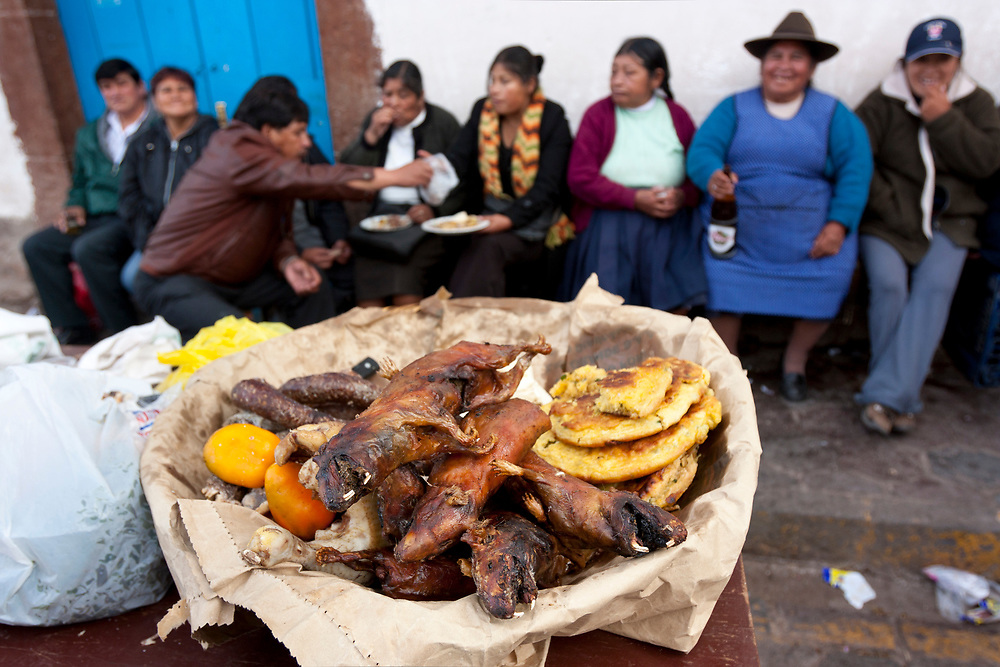 Cuy (guinea pigs) stacked up on the Plaza San Blas, with a row of happy / drunk townfolk enjoying forties of local beer. Cuzco, Peru.