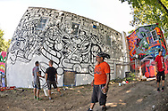 """Huntington, New York, U.S. 24th August 2013. Three world renowned street artists - PHETUS, MAS PAZ, and SONIC - are decorating with graffiti the rear walls of the Hunting Arts Council building, at the art event """"Off the Walls"""" Block Party, by SPARKBOOM, a project the council created to help emerging artists, showcase talents, and help its artistic family network. Taken with 180 degree fisheye lens."""