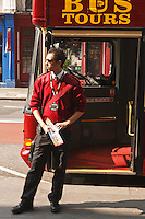 A Big Bus Tour salesman sells tickets for Hop-On Hop-Off double decker bus tours, London, England.