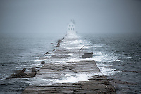 The closest moon approach in the last 70 years brought the tide up and over the top of the Rockland Breakwater on a misty, stormy day.
