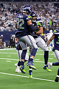 Seattle Seahawks outside linebacker K.J. Wright (50) leaps in the air and celebrates with Seattle Seahawks defensive tackle Nazair Jones (92) after Jones intercepts a fourth quarter pass in the end zone and stopping a Dallas Cowboys drive during the NFL football NFC wild card playoff game against the Dallas Cowboys on Saturday, Jan. 5, 2019 in Arlington, Tex. The Cowboys won the game 24-22. (©Paul Anthony Spinelli)