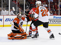 Oct 3, 2009; Newark, NJ, USA; Philadelphia Flyers goalie Ray Emery (29) makes a save while New Jersey Devils left wing Zach Parise (9) and Philadelphia Flyers defenseman Chris Pronger (20) battle for the loose puck during the second period at the Prudential Center.