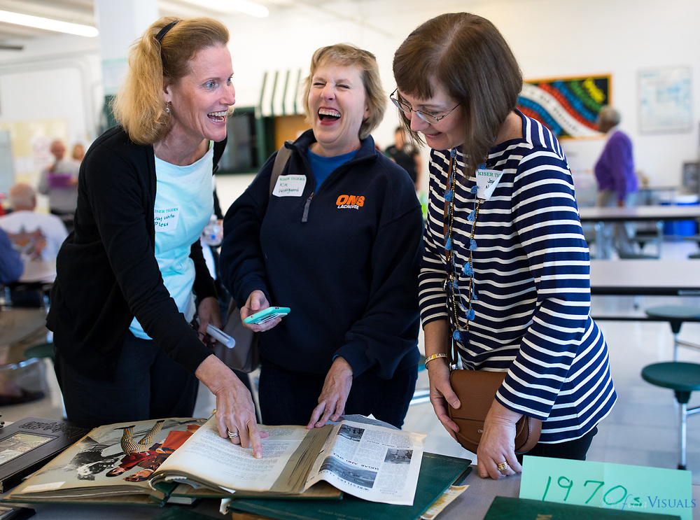 Lucy White Pless, left, Kim Westergaard and Joyce Nethery Kemmerer  laugh at a scrapbook which conveys the controversy of girls wanting to wear pants during 1969-1970.<br /> <br /> At least 50 alumni and two former teachers came together Saturday to celebrate the 60th anniversary of Kiser Middle School. The Kiser Alumni Association put together the celebrate to honor the school's recent accomplishments, its illustrious past and its newest milestone. Named after former mayor and school board chairman, Claude Kiser, the school turned 60 this year.<br /> <br /> Photographed, Saturday, October 28, 2017, in Greensboro, N.C. JERRY WOLFORD  / Perfecta Visuals
