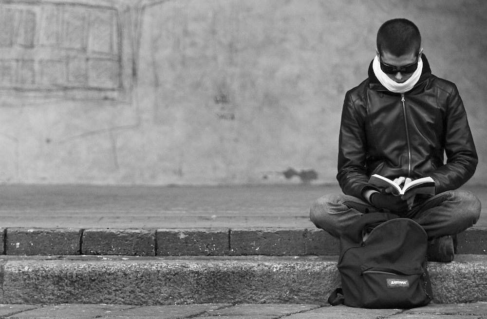 Black and white photography. A man reading in Bologna Italy.