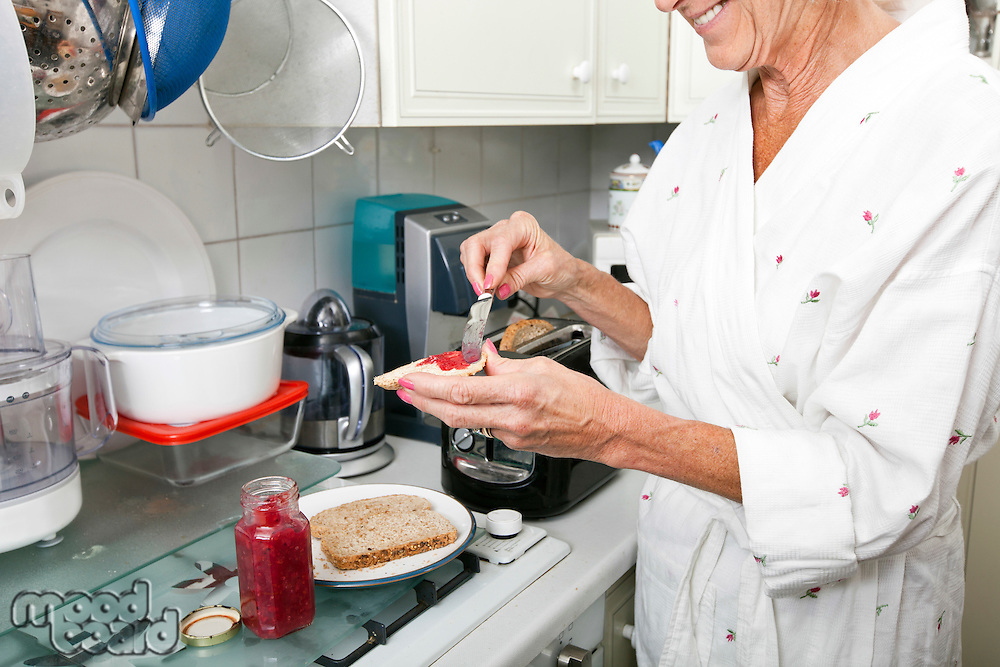 Midsection of senior woman applying jam on toast in kitchen