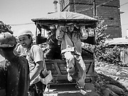 "15 FEBRUARY 2019 - SIHANOUKVILLE, CAMBODIA: A Chinese construction worker jumps out of a tuk-tuk that shuttles workers from their housing to the job site. There are about 80 Chinese casinos and resort hotels open in Sihanoukville and dozens more under construction. The casinos are changing the city, once a sleepy port on Southeast Asia's ""backpacker trail"" into a booming city. The change is coming with a cost though. Many Cambodian residents of Sihanoukville  have lost their homes to make way for the casinos and the jobs are going to Chinese workers, brought in to build casinos and work in the casinos.      PHOTO BY JACK KURTZ"