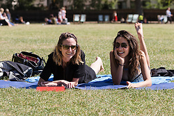 © Licensed to London News Pictures. 12/08/2016. LONDON, UK.  Friends, Alejaflak and Alejandra sunbathe during the hot and sunny weather today in St Gren Park in London.  Photo credit: Vickie Flores/LNP