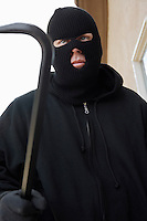 Man wearing balaclava and holding crowbar