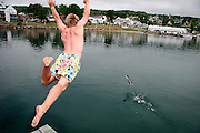 Jordon Woods-Wahl dives off the dock in Bayfield, Wisconsin attempting to catch a duck in flight during a lull in the wind during Bayfield Race Week 2007.
