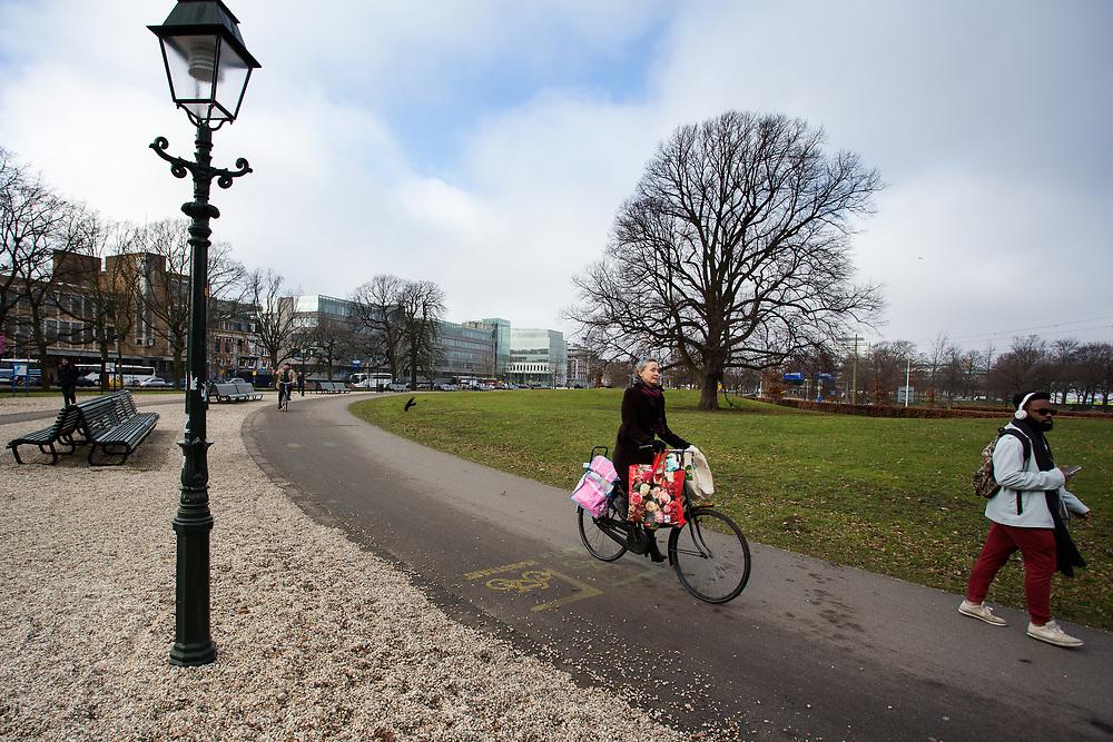 In Den Haag fietst een vrouw over het Malieveld.<br /> <br /> In The Hague cyclists ride at the city center.