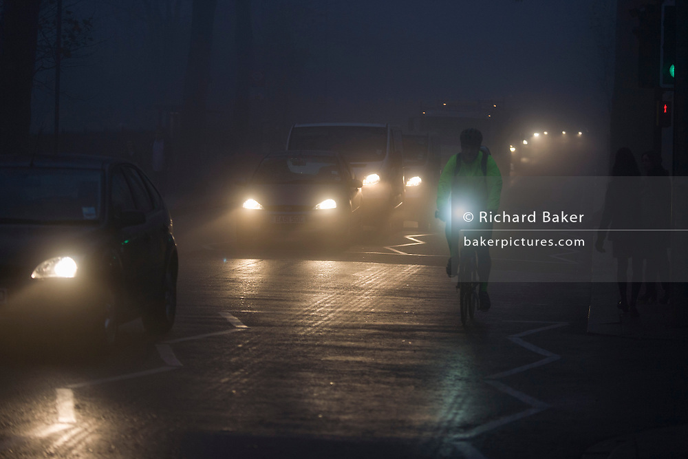 Cyclist and commuter traffic at dawn on a foggy morning in south London.