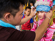 "04 APRIL 2015 - CHIANG MAI, CHIANG MAI, THAILAND:  A man helps a boy get into his ceremonial outfit for the Poi Sang Long Festival at Wat Pa Pao in Chiang Mai. The Poi Sang Long Festival (also called Poy Sang Long) is an ordination ceremony for Tai (also and commonly called Shan, though they prefer Tai) boys in the Shan State of Myanmar (Burma) and in Shan communities in western Thailand. Most Tai boys go into the monastery as novice monks at some point between the ages of seven and fourteen. This year seven boys were ordained at the Poi Sang Long ceremony at Wat Pa Pao in Chiang Mai. Poy Song Long is Tai (Shan) for ""Festival of the Jewel (or Crystal) Sons.     PHOTO BY JACK KURTZ"