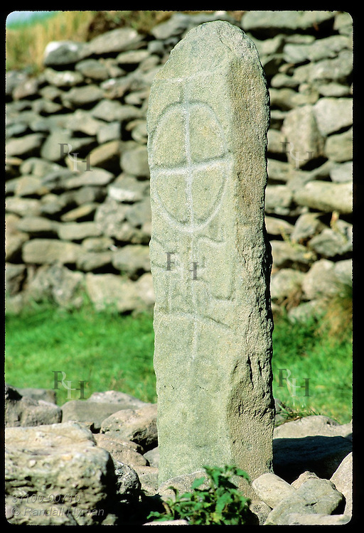 Early Christian pillar stone near Gallarus Oratory bears a Maltese Cross; Dingle Peninsula. Ireland