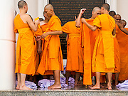 19 JULY 2014 - KHLONG LUANG, PATHUM THANI, THAILAND: Newly ordained monks and novices put on their robes for the first time at Wat Phra Dhammakaya. Seventy-seven men from 18 countries were ordained as Buddhist monks and novices at Wat Phra Dhammakaya, a Buddhist temple  north of Bangkok, Saturday. It is the center of the Dhammakaya Movement, a Buddhist sect founded in the 1970s and led by Phra Dhammachayo (Phrathepyanmahamuni). It is the largest temple in Thailand. The Dhammakaya sect has an active outreach program that attracts visitors from around the world.    PHOTO BY JACK KURTZ