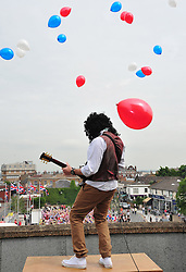 © Licensed to London News Pictures. 31/05/2012.Diamond Jubilee weekend has started early for 650 school children in Gravesend (today 31.05.2012).650 children from local schools in Gravesham join together in the largest street party in the UK for the Diamond Jubilee celebrations, held at The Civic Square in Gravesend, Kent.. Adrian Hickmott dressed as Brian May played the National anthem on top of the civic centre while the children waved their flags..Photo credit : Grant Falvey/LNP