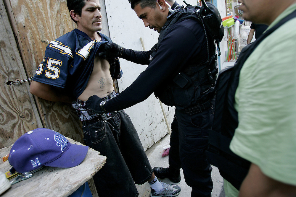 Tijuana Police agents search a man for illegal contraband during a drug sweep in Colonia Chula Vista  in Tijuana, Mexico.