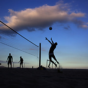 Locals play foot volley, a hybrid game combining beach volley ball and football at Copacabana beach, Rio de Janeiro,  Brazil. 5th July 2010. Photo Tim Clayton..The beaches of Rio de Janeiro, provide the ultimate playground for locals and tourists alike. Beach activity is in abundance as beach volley ball, football and a hybrid of the two, foot volley, are played day and night along the length and breadth of Rio's beaches. .Volleyball nets and football posts stretch along the cities coastline and are a hive of activity particularly at it's most famous beaches Copacabana and Ipanema. .The warm waters of the Atlantic Ocean provide the ideal conditions for a variety of water sports. Walkways along the edge of the beaches along with exercise stations and cycleways encourage sporting activity, even an outdoor gym is available at the Parque Do Arpoador overlooking the ocean. .On Sunday's the main roads along the beaches of Copacabana, Leblon and Ipanema are closed to traffic bringing out thousands of people of all ages to walk, run, jog, ride, skateboard and cycle more than 10 km of beachside roadway. .This sports mad city is about to become a worldwide sporting focus as they play host to the world's biggest sporting events with Brazil hosting the next Fifa World Cup in 2014 and Rio de Janeiro hosting the Olympic Games in 2016...