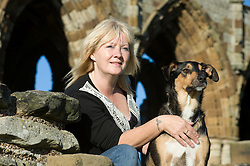 Attractive blonde woman poses with her dog at whitby abbey