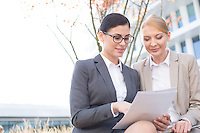 Businesswomen reading documents while sitting outdoors