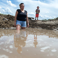 Lisa R. Benally stands in the spot where her car was washed off the road Sunday night in a storm. Benally was in the car with three other people including her son Elijah John Benally, 2, seen here on the right.