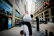 A man dressed up as a panda on his way to the street outside NYSE Euronext Stock Exchange to make some money out of tourists.
