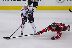 Mar 27; Newark, NJ, USA; Chicago Blackhawks center Patrick Sharp (10) makes a pass past a diving New Jersey Devils center Patrik Elias (26) during the third period at the Prudential Center. The Devils defeated the Blackhawks 2-1 in an overtime shootout.
