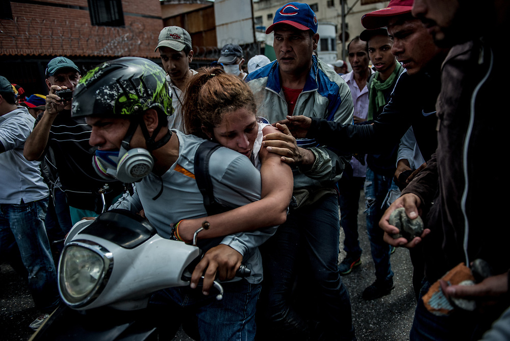 CARACAS, VENEZUELA - APRIL 19, 2017:  Protesters evacuate a female protester that had passed out on the back of a motorcycle.  Thousands of protesters took to the streets today in Venezuela to show their discontent with the government.  They were met by riot police that fired tear gas and rubber bullets at them.  Some protesters responded by throwing rocks and petrol bombs.  Venezuela is in crisis, and residents face daily struggles over food and medicine shortages, and one of the highest crime rates in the world.  PHOTO: Meridith Kohut