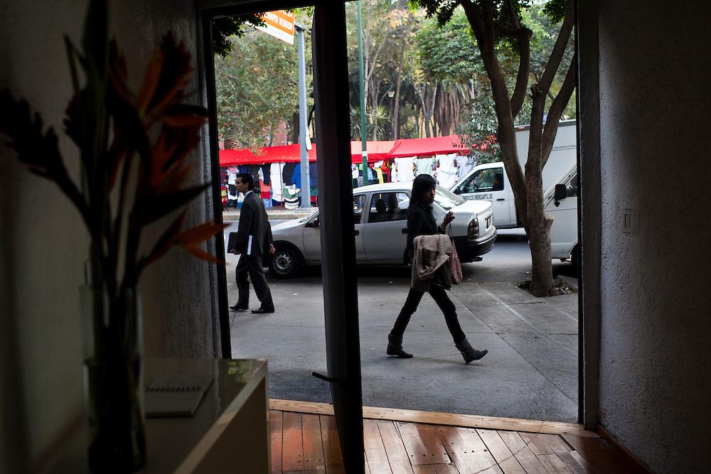 Pedestrians walk in front of El Eco Museum, as seen through the museum's front door, in Mexico City.