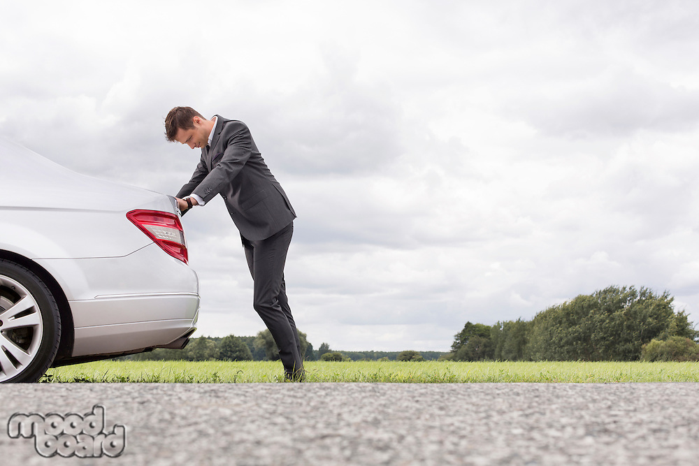 Side view of tired young businessman pushing car at countryside