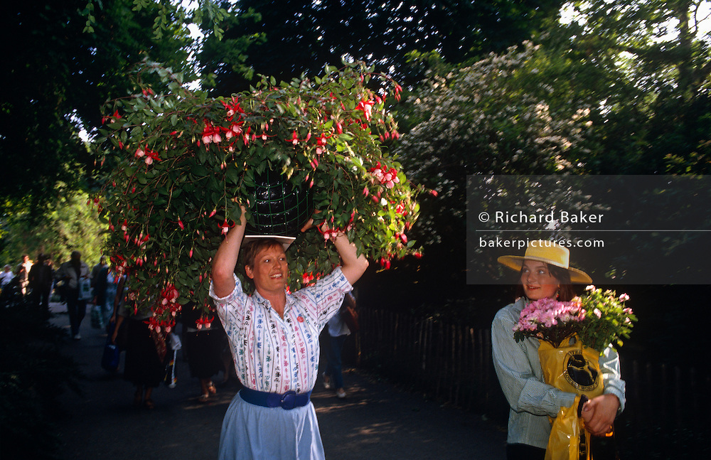 Balancing a huge basket of Fuchsias on her head, a lady walks along a Chelsea street accompanied by a friend after having just left the Chelsea Flower Show, in London England on the last day of the show when members of the Royal Horticultural Society and the general public are invited to purchase those plants and shrubs that have been displayed all week. It is the perfect summer May afternoon in west London, when lovers of horticulture have gathered from across the country to admire the ultimate in plants and flowers in the grounds of Chelsea Hospital. With its pink blooms hanging from the main bulk of the shrub, the Fuchsia is resplendent in the late sunshine, a scene of quintessential English gardens and long summer days.