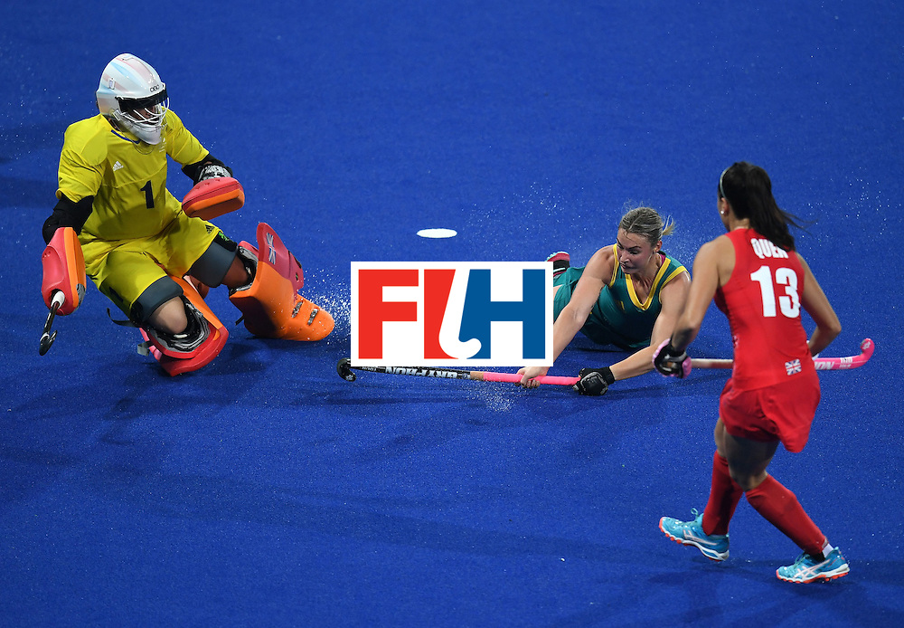 Australia's Mariah Williams (C) falls near Britain's Sam Quek (R) and goalkeeper   Maddie Hinch during the women's field hockey Britain vs Australia match of the Rio 2016 Olympics Games at the Olympic Hockey Centre in Rio de Janeiro on August, 6 2016. / AFP / MANAN VATSYAYANA        (Photo credit should read MANAN VATSYAYANA/AFP/Getty Images)