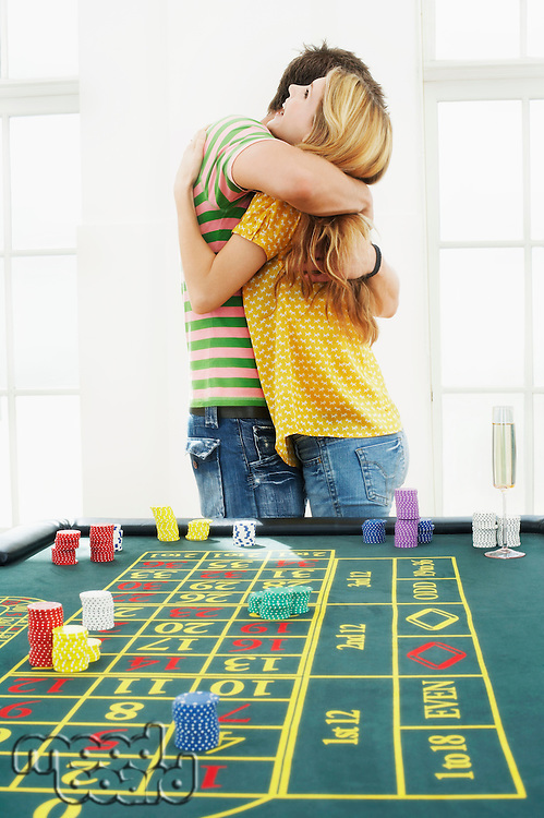 Young man hugging woman at roulette table
