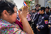 22 DECEMBER 2013 - BANGKOK, THAILAND: An anti-government protestor prays in front of riot police guarding the home of caretaker Prime Minister Yingluck Shinawatra. Hundreds of thousands of Thais gathered in Bangkok Sunday in a series of protests against the caretaker government of Yingluck Shinawatra. The protests are a continuation of protests that started in early November and have caused the dissolution of the Pheu Thai led government of Yingluck Shinawatra. Protestors congregated at home of Yingluck and launched a series of motorcades that effectively gridlocked the city. Yingluck was not home when protestors picketed her home.     PHOTO BY JACK KURTZ