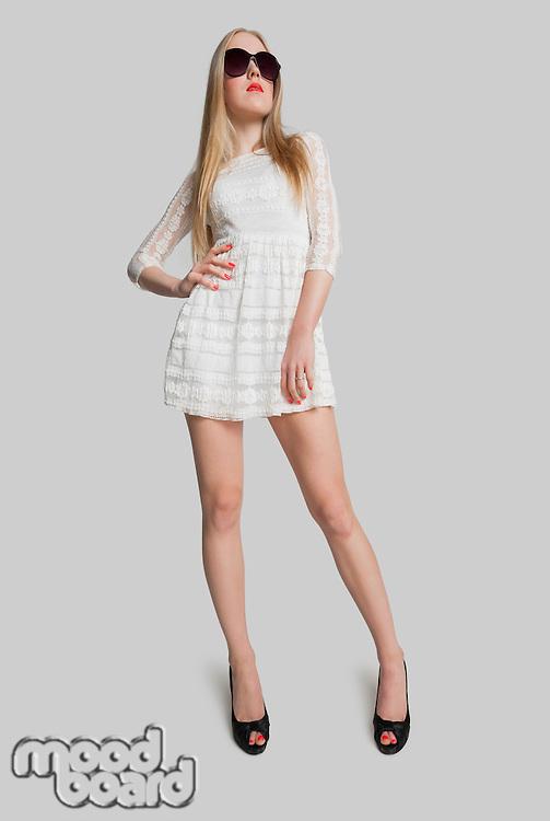 Full length stylish teenage girl posing over gray background