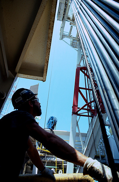 Stock photo of the driller on an offshore oil and gas drilling rig with his hand on the brake next to a full rack of drill pipe
