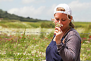 Young blonde female teen smells flows in a field of wildflowers