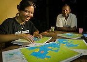 Conservation Fellow Wida Sulistyaningrum and community member Bram Wariensi prepare puzzles from maps of Triton Bay no-take zones designated by local communities.