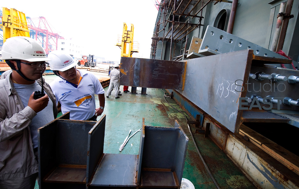 Workers check OBG 14W is safely loaded on board a Zhenhua ship, prior to the last steel voyage, in Changxing Island, near Shanghai, on July 18, 2011. Photo by Lucas Schifres/Pictobank