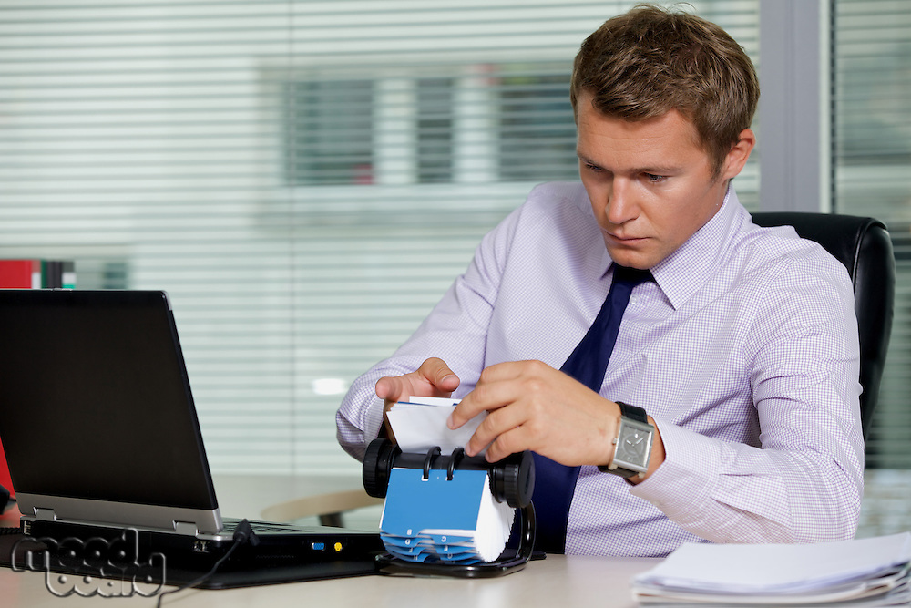 Businessman searching for card by laptop in office