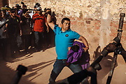 Un hombre golpea a los judíos con una soga mientras protege a un niño que representa al niño Jesús durante la representación de las 12 estaciones en Huaynamota, Nayarit.